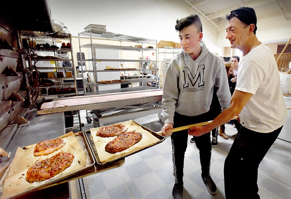 BRYAN EATON/Staff Photo. Malatesta helps Cote Gabardi, 14, with a huge baker's peel to take some of the pizza from the oven for cooling.