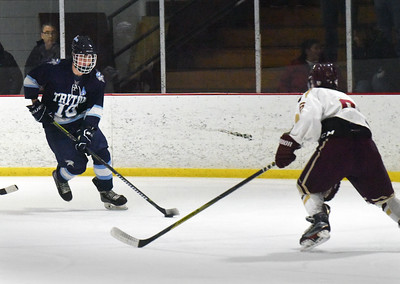 BRYAN EATON/Staff photo. Triton's Connor Kohan moves the puck as Charles Forrest defends.