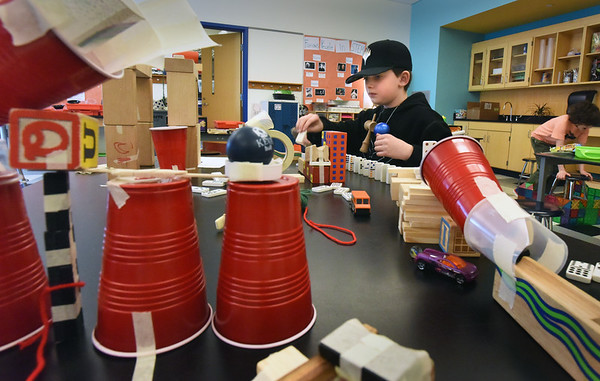 BRYAN EATON/Staff Photo. Lucas Itrato, 10, works on his Rube Goldberg invention called Snack Time which ends up putting a cracker in his mouth at the end of a shoot. He was in Kristen Spinney's STEM class at the Bresnahan School, one of the school vacation week activities run by the Newburyport Youth Services.