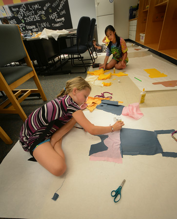 JIM VAIKNORAS/Staff photo Haley Miller, 9, and Amy Nguyen, 10, use glue and fabric to decorate doppelganger they traced at Summer Kids Club at the Salisbury Elementary Club Monday. The kids were learning about the Old West and created the art work to represent themselves in that time period.