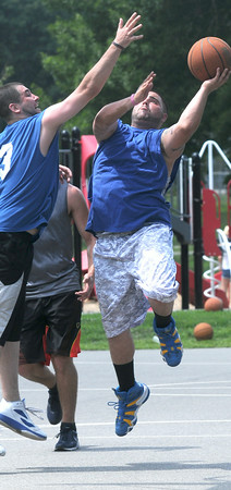 JIM VAIKNORAS/Staff photo Matt Scalesse drives to the hoop during the The CarriageTown ThrowDown Saturday at Amesbury Park. Proceeds from the 3 on 3 basketball tournament went to the
