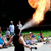 JIM VAIKNORAS/Staff photo Benjamin Reynolds entertains the crowd at the YWCA Summer Fun Series at the Childrens Center on Pond Street in Newburyport Thursday. Reynolds perform thrilling acts of pyrotechics including eating, breathing, and twirling fire.