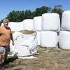 BRYAN EATON/Staff photo. Mark Pender with bales of hay at his Amesbury farm.