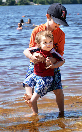 BRYAN EATON/Staff photo. Alex Wolkowvich, 8, of Newburyport dips the feet of his cousin, William Downs, 18 months, of Amesbury into the water at Lake Gardner Beach in Amesbury on Wednesday afternoon. The weather stays beautiful into the weekend with showers possible on Sunday and Monday.