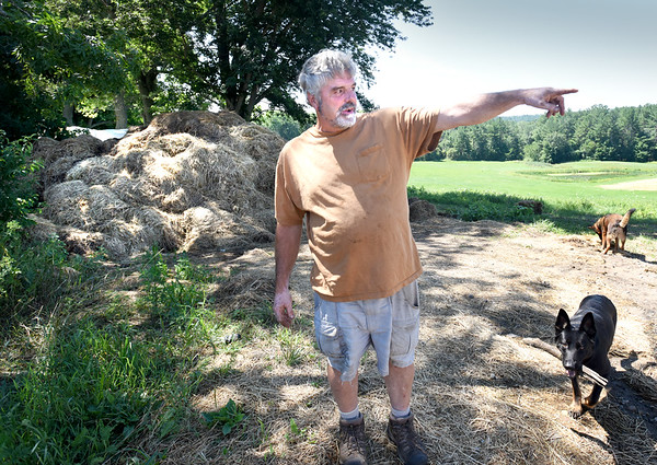 BRYAN EATON/Staff photo. Amesbury farm owner Mark Pender in front of compost which has a neighbor complaining to town officials.