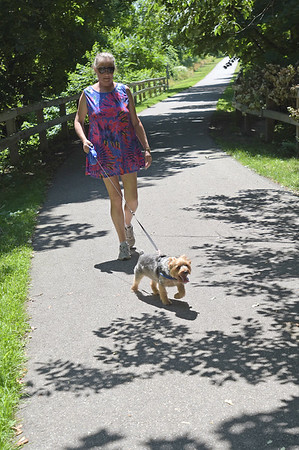 TIM JEAN/Staff photo<br /> <br /> Laurie Frohlich, of Salisbury walks her dog Stinky, along the Old Eastern Marsh Rail Trail in Salisbury. Work on connecting the Clipper City Trail in Newburport and the Ghost trail in Salisbury will soon begin. 7/9/18