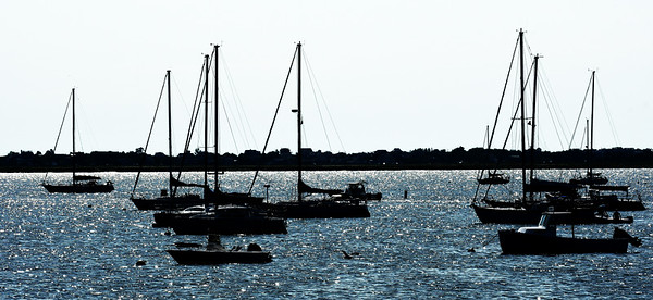 JIM VAIKNORAS/Staff photo Sail boats, with sales furled, sit in the morning sunshine off Salisbury Town Pier Sunday.