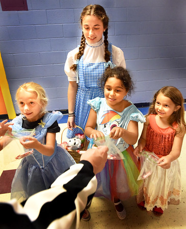 BRYAN EATON/Staff photo. The Boys and Girls Club in Salisbury is holding Holiday Madness Week with Tuesday being the day to celebrate Halloween. Stopping by the computer room to get Trick or Treat goodies from staff are, from left, Khloe Chase, 6, as Cinderella; counselor-in-training Rachel Dion, as Dorothy from the Wizard of Oz; Alivia Lee, 6, as Rainbow Dash and Amarah Boudreau, 5, as Moana from the Disney movie.