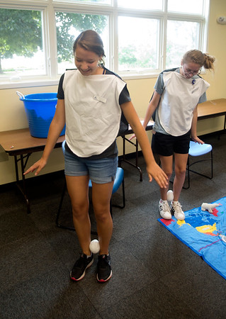JIM VAIKNORAS/Staff photo Interns Ellie Kerns and Molly Balentine demonstrate how penguins walk with their eggs  at the Joppa Flats Education Center in Newbury Sunday.