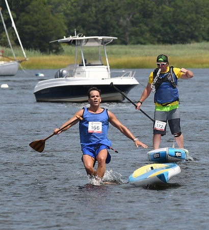 JIM VAIKNORAS/Staff photo Chris Williamson jumps off his board as Scott Tyrell spits out water at the 3rd annual Yankee Homecoming Kayak and SUP River Race at Cashman Park in Newburyport Saturday.