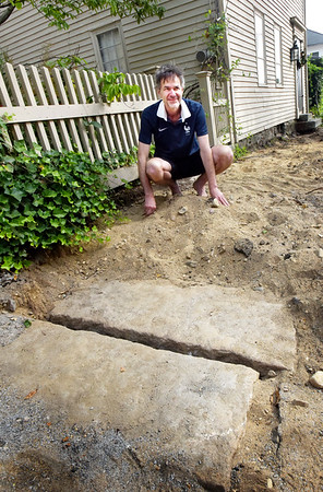 BRYAN EATON/Staff photo. Newburyport city crews putting in new sidewalks on Dove Street came upon these two slabs in front of the home of Dominique Clement, pictured, and Patricia Peknik. Underneath the slabs are a cistern that could date back over 200 years.