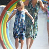 JIM VAIKNORAS/Staff photo Anna Shoulimas, 8, of South Hampton, and her Nana Laura Dandea of Amesbury cool of at the Amesbury Park Splash Pad Wednesday morning.