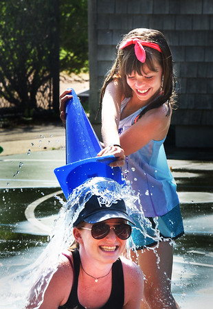 "BRYAN EATON/Staff photo. Samantha Glynn, 9, unloads a cone of water on Newburyport Youth Service counselor Sam Orlando at Clipper Kids camp at Perkins Playground on Tuesday morning. They were playing the cooling game of ""Drip, Drip, Drop"" where the person who's ""it"" walks the circle of youngsters dripping water on them and then drops the main load on the next person who's it."