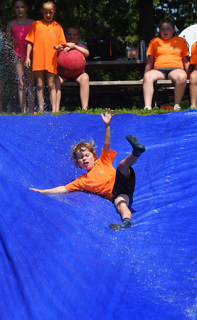 BRYAN EATON/Staff photo. Max Morris, 7, goes down the water slide at the Newburyport Youth Services' Clipper Kids camp at Perkins Park which they set up every Friday, which was fitting during the hot and humid weather. The weather stays nice into the weekend with slight chance of shower Saturday and Sunday looking spectacular and less humid according to forecasters; good new for Yankee Homecoming events.