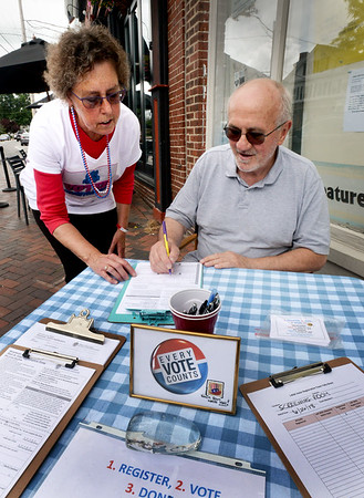 BRYAN EATON/Staff photo. Betty Breau of I-RISE looks on as Andrew Mungo fills out a voter registration form. Her group will be in front of the Screening Room at times during Yankee Homecoming help others do the same.