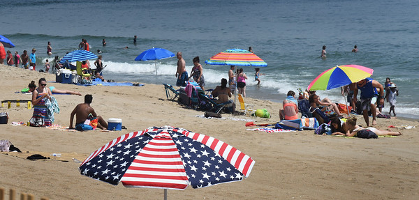 BRYAN EATON/Staff photo. One sun umbrella at Salisbury Beach was timely with its patriotic pattern of the American Flag. Umbrellas should be plentiful today as the beaches will be crowded and the weather, hot.