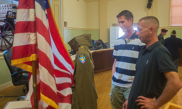 JIM VAIKNORAS/Staff photo Daniel and Steven Salamon look over their grandfather Stanley Kawa's World War 2 uniform at Amesbury City Hall. The uniform was purchased on Ebay and formally presented to the family Saturday.