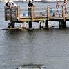 JIM VAIKNORAS/Staff photo People on the fishing pier at Cashman Park in Newburyport look at a car that was driving into the river Sunday afternoon.