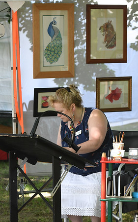 JIM VAIKNORAS/Staff photo Artist Tina Gagnon paints as she sells her art at Yankee Homecoming's Art on the Bartlet Mall Sunday at the Bartlet Mall in Newburyport.