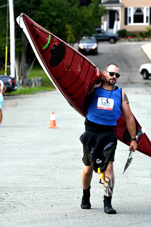 JIM VAIKNORAS/Staff photo Elite division 2nd place finisher Scott Morse carries his kayak to the start the 3rd annual Yankee Homecoming Kayak and SUP River Race at Cashman Park in Newburyport Saturday.