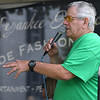 JIM VAIKNORAS/Staff photo Volunteer Jim Cate entertains the crowd by singing songs during sound check before Yankee Homecoming opening ceremonies Sunday at the Bartlet Mall in Newburyport.