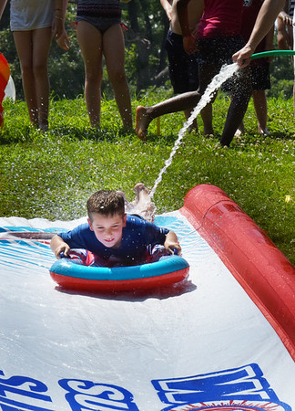 BRYAN EATON/Staff photo. Jack Enderwick, 7, heads down the water slide at Amesbury Town Park in the town's Recreation Department's Youth Park Program. Other programs include swimming, boating and nature studies at Camp Kent among others.
