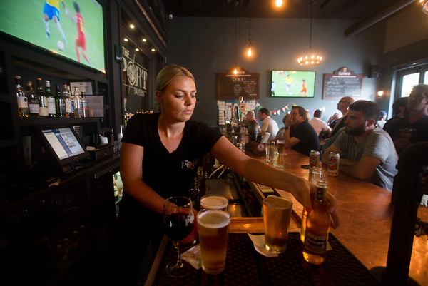 JIM VAIKNORAS/Staff photo Ashley Griffin serves drinks a the Port Tavern in Newburyport Friday afternoon, as patrons watch Belgium play Brazil in the World Cup. The tournament has been very popular with local soccer fans.