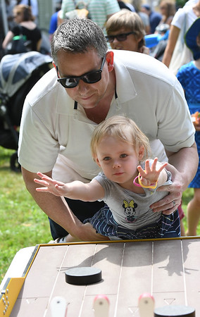 JIM VAIKNORAS/Staff photo Ellie Hatch, 3, from Newburyport gets some help from her dad Mike as she tries to knock down pins with a puck at Yankee Homecoming Old-Fashioned Sunday at the Bartlet Mall in Newburyport.
