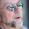 JIM VAIKNORAS/Staff photo The scene at the Tannery in Newburypor is reflected in the sunglasses of singer Jerry Short as he performs at the weekly Farmer Market Sunday morning.