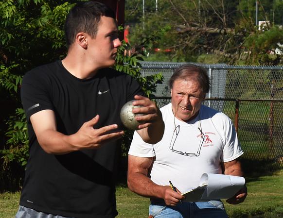 BRYAN EATON/Staff photo. Keith Walton looks on as Jake Boland throws a shot put.