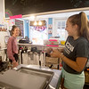 JIM VAIKNORAS/Staff photo Emma Richardson scoops out a cone of Purple Cow ice cream as she shares a laugh with fellow employee Emily Patterson at Simply Sweet in Newburyport Sunday afternoon.