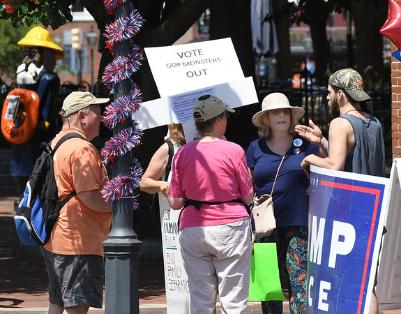 JIM VAIKNORAS/Staff photo John Parks carries a Trump/Pence sign as he talks with some of the more than one hundred people in Market Square in Newburyport Saturday  protesting President Trump's immigration policies.