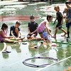 BRYAN EATON/Staff photo. Youngsters at the Clipper Kids Camp which meets at the Perkins Playground cool off with sprinklers after playing games in the field nearby. The camp, run by the Newburyport Department of Youth Services is one of many for the summer which includes basketball, tennis, Legos, sewing, swimming, etc.