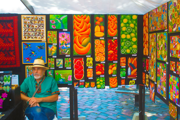 JIM VAIKNORAS/Staff photo Imre Kepes in front of work made by Guatemalan artists at the Cultural Survival Bazaar in Market Square in Newburyport Saturday. Artisans from all over the world  sold item ranging from flutes to art work to clothing and textiles.