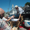 JIM VAIKNORAS/Staff photo Ward Emanualson serves hot dogs he grilled on the back of his truck at a free community picnic put on by the Old South Church Sunday morning at Atwood Park.