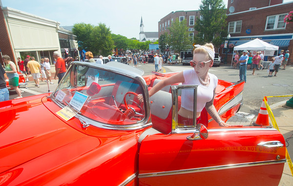 JIM VAIKNORAS/Staff photo Jennifer Turcotte, who showed up dressed for the occasion, steps into  a 1957 Bel Air convertable belonging to John Ross at the Amesbury Days Carriagetown Car Show in Market Square.