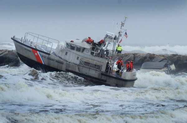 BRYAN EATON/Staff photo. Coast Guard Station Merrimack crew look for a person who was on the boat at right, stuck on the jetty, as another was rescued at Salisbury Beach at the mouth of the Merrimack River late Tuesday afternoon.