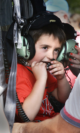 BRYAN EATON/Staff photo. Benjamin Grelle, 5, of Newburyport checks out the headset and microphone in the Blackhawk helicopter.