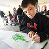 "BRYAN EATON/Staff photo. Aidan Gardner, 10, of Horseheads, N.Y. and visiting with cousins in Amesbury this weekend, was one of several writing letters to Amesbury's Jonathan Kukene and his army unit in Afghanistan. He was at Cider Hill Farm's National Donut Day which was established by the Salvation Army in 1938 to honor the ""dough lassies,"" female volunteers who made donuts for soldiers serving overseas. The farm is sending their cider donuts to Kukene and his comrades along with the letters."