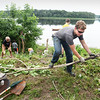 BRYAN EATON/Staff photo. Oliver Broderick, front, organized volunteers to clear brush and debris at Lowell's Boat Shop in Amesbury on Tuesday and is going to build a fence at the parking area and plant winterberries. The project is for his community service project to become an Eagle Scout in Troop 313 in Berwick, Maine where he lived--and remains a member--until his family moved to Amesbury across the street from the working boatbuilding museum.