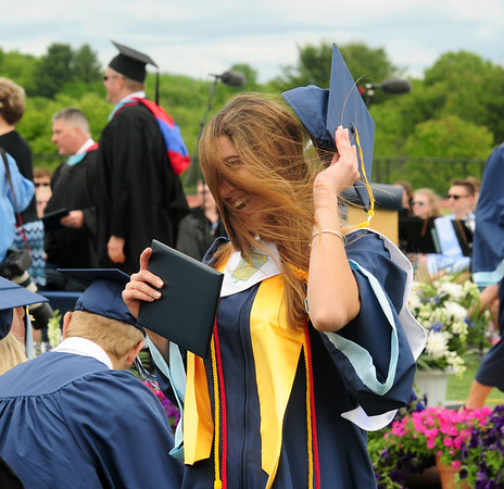 JIM VAIKNORAS/staff photo Triton Graduate Nicole Cordeau holds her hat after getting her diploma as a gust of wind kicks up  at commencement exercises in Byfield Saturday.