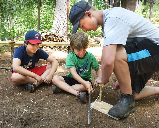 BRYAN EATON/Staff photo. Merrohawke Nature School counselor Corey Logan of Newburyport shows brothers, Henry Chisholm, 6, center, and Benny, 8, how fire was made before matches using a bow twisting wood into a board.
