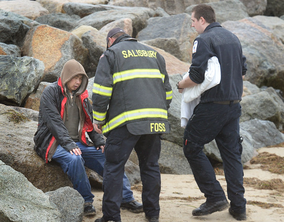 BRYAN EATON/Staff photo. A Salisbury firefighter tends to the passenger of a boat that capsized and got hung up on the north jetty of the Merrimack River with awaiting EMT's. Another person was still missing from the boat as of press time.