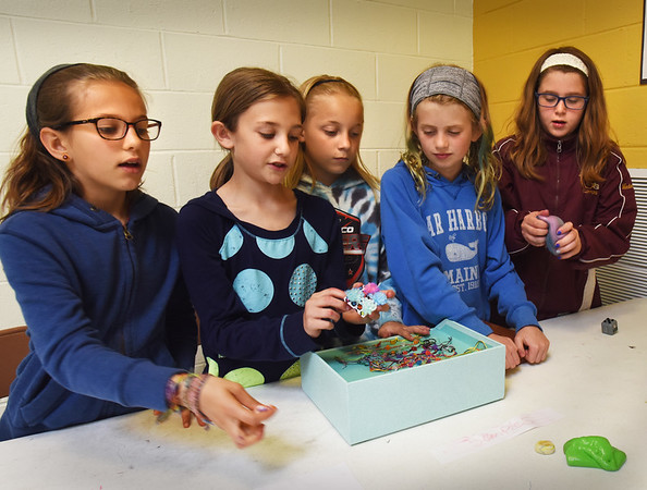 BRYAN EATON/Staff photo. Five friends at the Molin Upper Elementary School in Newburyport made fidget spinners, fidget bracelets and a couple items to sell to students during lunch to raise money for the American Cancer Society. Showing off there goods to students, from left, Maia Maylor, 9, Audrey Shepard, 9, Natalie DeGraves, 10, Emma MacIsaac, 10, and Emily Medeiros, 10.
