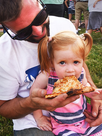 BRYAN EATON/Staff photo. Harper Pelletier, 2, with dad, Ryan, digs in to a slice of pizza from Flatbreads.