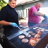 BRYAN EATON/Staff photo. Salisbury firefighter John Condelli, left, and Lt. Michael Merritt get the heat and smoke as they man the grill at the Hilton Senior Center. The department was putting on the cookout for the senior citizens after the Salad Toss Contest.