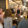 JIM VAIKNORAS/Staff photo <br /> Tanya Tzitzon, on the right, owner of the Markey Square Bakehouse in Amesbury, talks with customers, from the left, John Magnifico, Lynne Brillard, and Matt Cherrill.