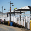 BRYAN EATON/Staff photo. Workers install roofs over sitting areas along Salisbury Beach's boardwalk.