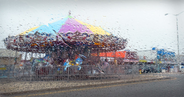 BRYAN EATON/Staff photo. Colors from the carousel brighten up an otherwise dreary day at Salisbury Beach as seen through a rain-covered windshield on Monday. Rain continues Tuesday with brightening skies on Wednesday and temperatures warming for the weekend.