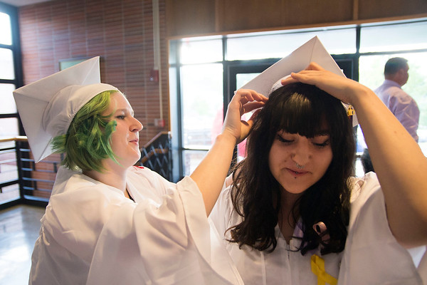 JIM VAIKNORAS/staff photo Sierra Gibbas, left, helps fellow senior Sarah Sylvester with her cap as they get ready for Friday nights graduation at Landry Stadium. Next year Sarah will be attending Southern New Hampshire University in Manchester and Sierra is headed to Northern Essex.